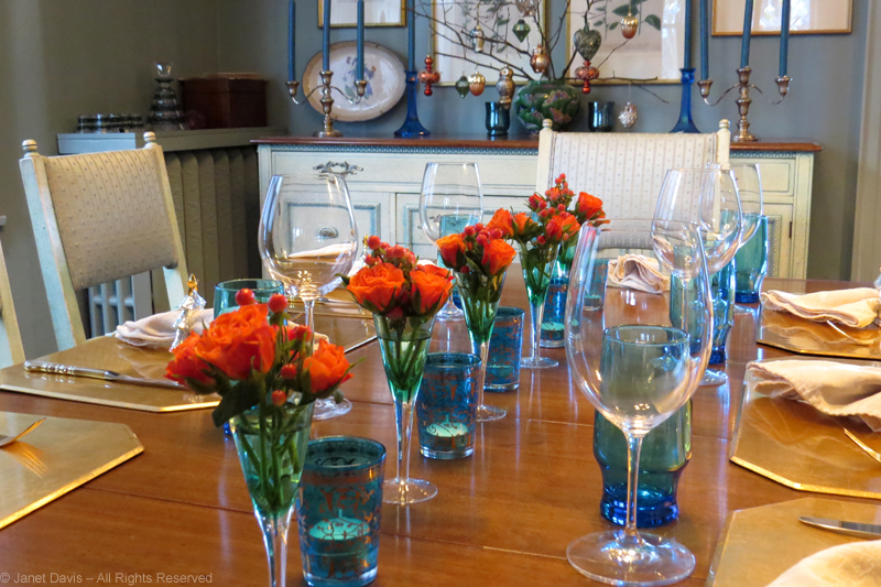 Orange sweetheart roses lined up with candles on my December table.
